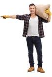Manlig bonde som rymmer en säck och peka för säckväv royaltyfri fotografi