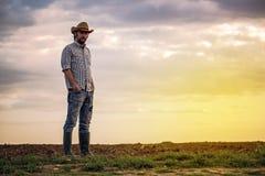 Manlig bonde Standing på fertil jordbruks- jord för lantgårdland