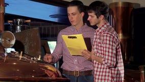 Manlig bryggare och hans medarbetare som undersöker brygga maskinen på ölproduktion arkivfilmer