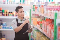 Manlig butiksinnehavare som arbetar i en livsmedelsbutik arkivfoton