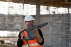 Manlig byggnadsarbetare som använder tryckluftsborren Royaltyfri Fotografi