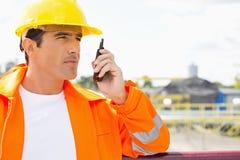 Manlig byggnadsarbetare som meddelar på walkie-talkie på platsen Royaltyfria Bilder