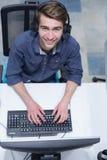 Manlig call centeroperatör som gör hans bästa sikt för jobb royaltyfri bild