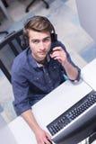 Manlig call centeroperatör som gör hans bästa sikt för jobb fotografering för bildbyråer