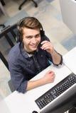 Manlig call centeroperatör som gör hans bästa sikt för jobb royaltyfri fotografi