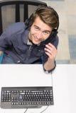 Manlig call centeroperatör som gör hans bästa sikt för jobb royaltyfria foton