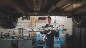 Manlig caucasian arbetare - mekanikern i bilgarage som reparerar seminariet - under lyftbilen Royaltyfria Foton