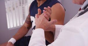 Manlig caucasian doktor som kontrollerar handleden av manlig afrikansk sportathl royaltyfri fotografi