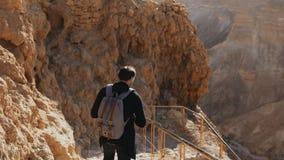 Manlig Caucasian turist på den forntida bergvägen Mannen med smartphonen och kameran tycker om den historiska öknen Israel fördär lager videofilmer