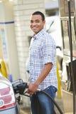 Manlig chaufförFilling Car At bensinstation Arkivfoto