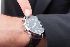 Manlig chef som pekar klockan i closeup arkivbild