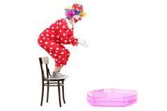 Manlig clown som förbereder sig att hoppa in i en liten pöl Royaltyfri Bild
