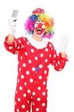 Manlig clown som tar en selfie och gör en gest med handen Arkivbilder