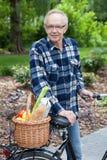 Manlig cyklist med den vide- korgen som är full av livsmedel fotografering för bildbyråer