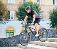Manlig cyklist som går ner konkret trappa royaltyfri bild