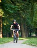 Manlig cyklistutbildning i gräsplan parkerar royaltyfri fotografi