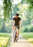 Manlig cyklistutbildning i gräsplan parkerar royaltyfri foto