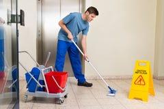 Manlig dörrvakt Mopping Floor Royaltyfria Foton