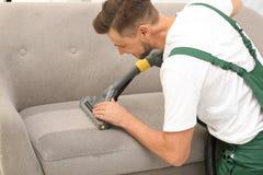 Manlig dörrvakt som tar bort smuts från soffan arkivfoto
