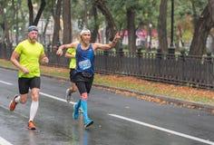 Manlig deltagare som pekar till andra personer på denväntade på mållinjen, medan köra på en stadsgata under 21 km avstånd arkivbild