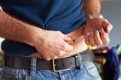Manlig diabetiker som injicerar sig med insulin Arkivbild