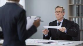 Manlig direktör som ser den ilskna assistenten, anställningavslutning, fattig kapacitet lager videofilmer