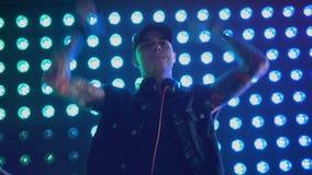 Manlig discjockey som sjunger och dansar, medan spela musik lager videofilmer