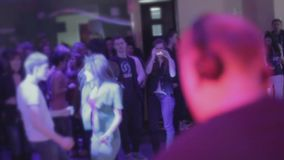 Manlig discjockey som utför på nattklubben, offentligt rörande på dancefloor lager videofilmer