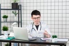 Manlig doktor i det vita laget med stetoskopet över hans hals som sitter på tabellen som tänker på receptet som skriver något fotografering för bildbyråer