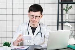 Manlig doktor i det vita laget med stetoskopet över hans hals som sitter på tabellen som tänker på receptet som skriver något royaltyfri foto