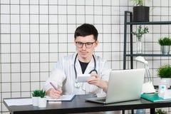 Manlig doktor i det vita laget med stetoskopet över hans hals som sitter på tabellen som tänker på receptet som skriver något arkivfoton