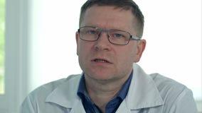 Manlig doktor i exponeringsglas som talar till kameran lager videofilmer