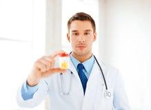 Manlig doktor med kruset av kapslar Arkivfoto