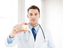 Manlig doktor med kruset av kapslar Arkivbilder