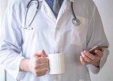 Manlig doktor med mobiltelefonen och koppen kaffe Royaltyfri Foto
