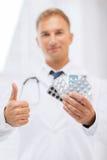 Manlig doktor med packar av preventivpillerar Royaltyfri Fotografi