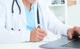 Manlig doktor, medicinare eller kirurg som använder bärbara datorn under konferensen Vård- kontroll med service för digitalt syst royaltyfri bild