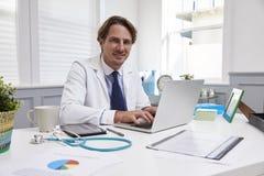 Manlig doktor Sitting At Desk som i regeringsställning arbetar på bärbara datorn arkivbild