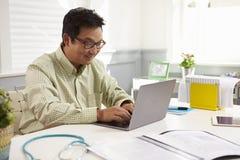 Manlig doktor Sitting At Desk som i regeringsställning arbetar på bärbara datorn arkivfoto