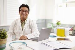 Manlig doktor Sitting At Desk som i regeringsställning arbetar på bärbara datorn arkivfoton