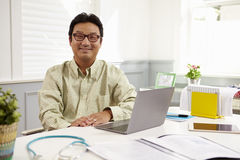 Manlig doktor Sitting At Desk som i regeringsställning arbetar på bärbara datorn royaltyfria bilder