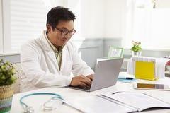 Manlig doktor Sitting At Desk som i regeringsställning arbetar på bärbara datorn fotografering för bildbyråer
