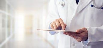 Manlig doktor som använder hans digitala minnestavla arkivbilder