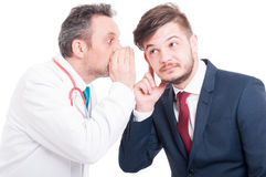 Manlig doktor som berättar en hemlighet till den nyfikna affärsmannen Arkivfoto
