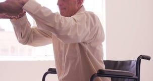 Manlig doktor som hjälper den höga mannen för att få upp från rullstolen arkivfilmer