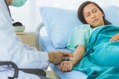 Manlig doktor som injicerar medicin f?r kvinnlig patient royaltyfria bilder