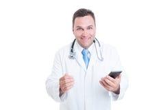 Manlig doktor som känner sig lyckligt och upphetsat innehav en telefon Royaltyfri Fotografi