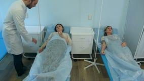 Manlig doktor som kontrollerar två kvinnliga patienter på droppande som vilar i sängar arkivfilmer