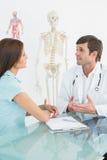 Manlig doktor som lyssnar till patienten med koncentration på skrivbordet arkivfoto