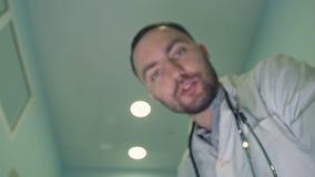 Manlig doktor som ner ser på patienten som försöker att lugna honom eller henne lager videofilmer
